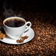 图库照片: White cup of hot coffee on coffee beans
