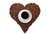 White cup of coffee on heart shaped coffee beans — Stock Photo