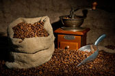 Sack of coffee beans, coffee-grinder and metal scoop still life — Stock Photo