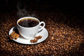 White cup of hot coffee on coffee beans — Stock Photo