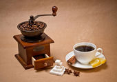 Coffee-grinder and cup of hot coffee — Stock Photo