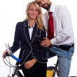 Young Businessman and Businesswoman on a Bike - Stock Photo