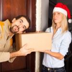 男子戴圣诞帽的年轻女子从接收一个框 — 图库照片