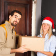 Man Receive a Box from Young Woman with Christmas Hat - Stock Photo