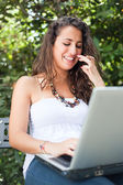 Girl Typing on a Bench in the Park — Stockfoto