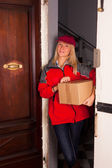 Female Courier at the Door with a Box — Stock Photo