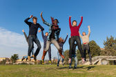 Group of Happy College Students Jumping at Park — Stockfoto