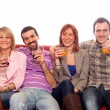 Young Group Sitting on Sofa and Drinking — Stock Photo #5074381