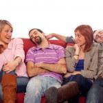 Girls Laughing while Boys Sleep on Sofa — Stock Photo #5078247