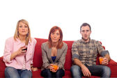 молодые группы, сидя на диване и пить — Стоковое фото