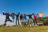 Group of Happy College Students Jumping at Park — Stock Photo