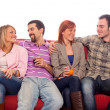 Stock Photo: Young Group Sitting on Sofa and Drinking