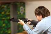 Woman is aiming by air rifle — Stock Photo