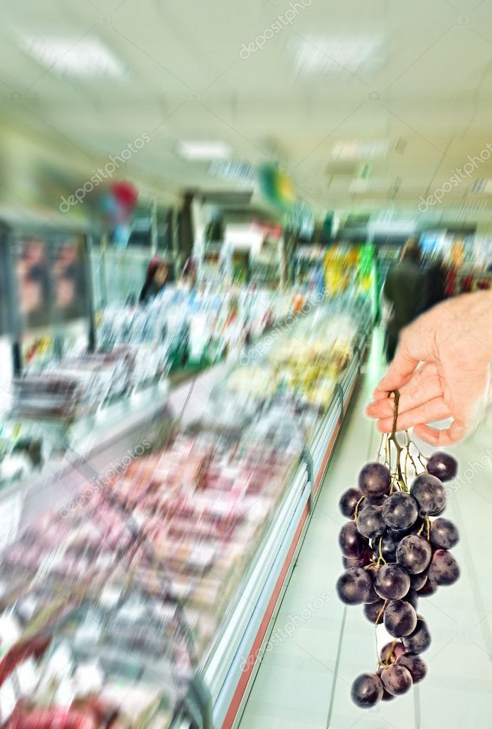 Hand with grapevine among supermarket — Stock Photo #4337238