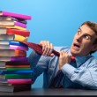 Stock Photo: Man looking at a stack of books