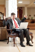 Smiling man with notebook in chair — Stock Photo