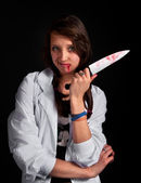 Angry nurse with bloody knife over black — Stock Photo