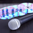 Microphone and cd disks on black table — Stock Photo #4307368