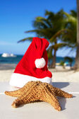 Santa hat and starfish on beach — Stock Photo