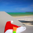 Santa Hat and sun tan on chaise longue — Stock Photo