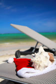 Santa Hat and seashell on chaise longue on beach — Stock Photo