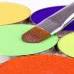 Professional make-up brush on green eye shadows palette — Stock Photo