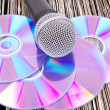 Microphone and compact disks on vinyl records - Stockfoto
