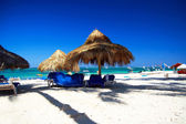 Caribbean white beach and grass umbrella — Stock Photo
