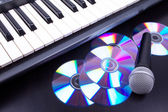 Vocal microphone,cd discs and electronic keyboard. Closeup on bl — Stock Photo