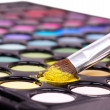 Professional make-up brush on yellow eye shadow palette - Stock Photo