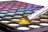 Professional make-up brush on yellow eye shadow palette — Stock Photo
