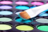 Make-up brush in blue eyeshadows — Stock Photo