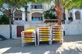 Stack of yellow deck-chairs on beach — 图库照片