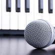 Microphone on piano keyboard background - Stockfoto
