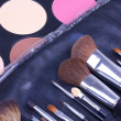 Stock Photo: Make-up brushes in leather case on eyeshadows palettes