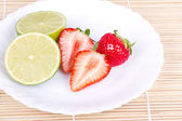 Strawberries and lime on white plate — Stock Photo