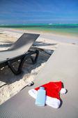 Santa Hat and sun tan on chaise longue — Stock Photo