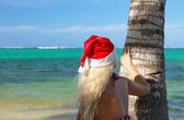 Blond lady in Santa hat near palm — Stock Photo