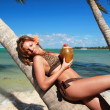 Woman in bikini resting on palm with cocnut — Stock Photo