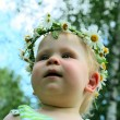 Stock Photo: Happy little girl in flowers wreath lying on green meadow