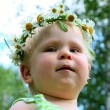 Happy little girl in flowers wreath lying on green meadow — Stock Photo