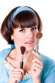 Woman in blue dress with two make-up brushes — Stock Photo