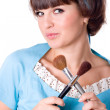 Brunet woman with two make-up brushes - Stock Photo