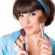Woman in blue dress with two make-up brushes - Stock Photo