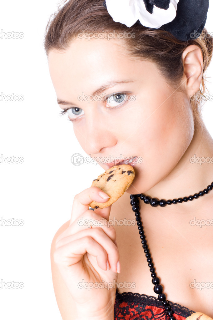 Portrait of young attractive woman in corset and little hat eating cookie on white background — Stock Photo #4772440