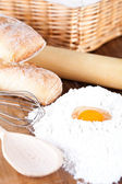 Still life of bread, flour, eggs and kitchen utensil — Stock Photo