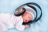 The newborn kid listening to music — Stock Photo