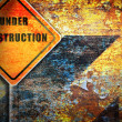Roadsign under construction rusty wall. — Stockfoto