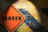 Traffic sign danger rusty wall background. — Stockfoto