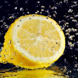 Half of lemon with stopped motion water drops on black — Stock Photo